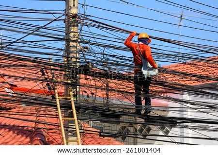 Pattaya, Thailand - Mar 9, 2015 - An unidentified man works on electric wires to install the household cable wires network  - stock photo