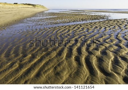 Pattern in sand caused by Atlantic tide along beach in Cape Cod, Massachusetts, about an hour after sunrise - stock photo