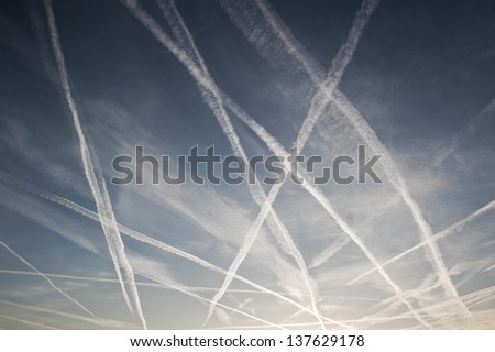 Pattern of airplane trails of condensed air crisscrossing each other against the blue sky - stock photo