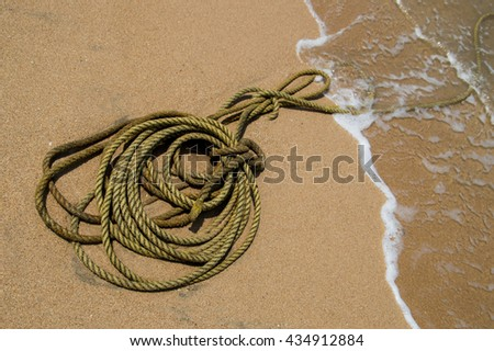 pattern of bright sand beach with motion blur sea wave and a hemp rope on it - stock photo