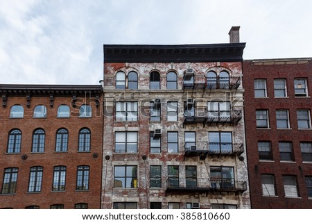 Pattern of fire escapes and window air conditioning units  on side of older brick building in New York City