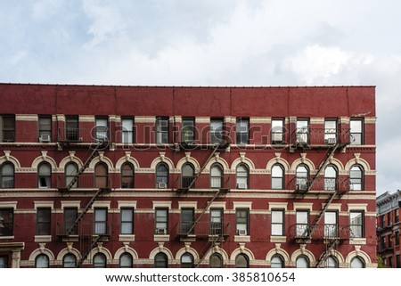 Pattern of fire escapes on side of older ornate brick building in New York City