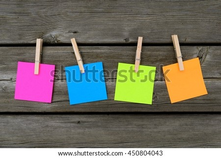 pattern of four colorful sticky notes placed on a wooden deck