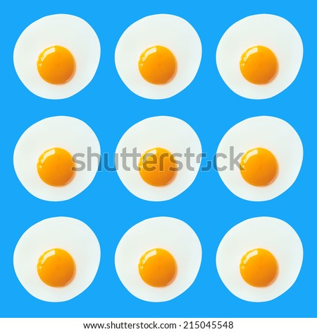 Pattern of fried eggs on blue sky background - stock photo