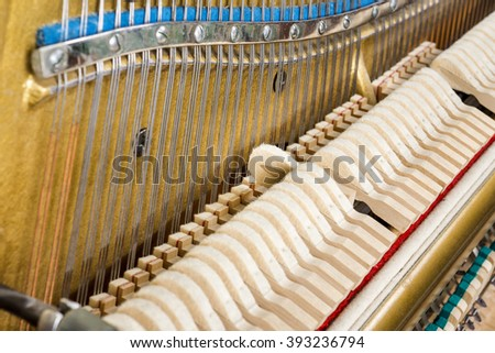 Pattern of hammers and strings inside piano, close up. One hummer in action while key is pressed. Stand out from the crowd concept. - stock photo