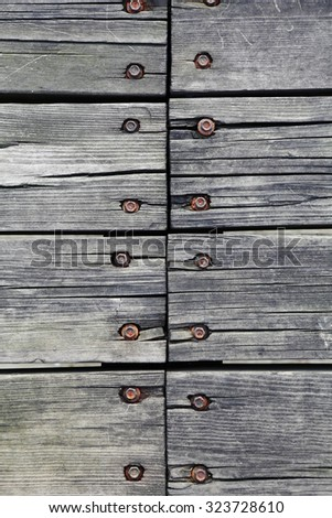 Pattern of screws and bolts joining wooden planks. - stock photo