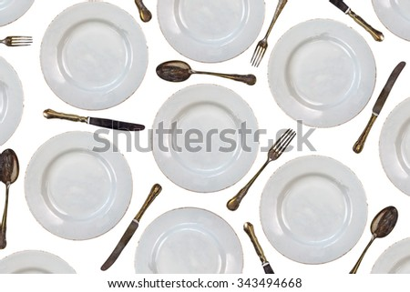 Pattern of vintage dinner plates, knives, forks and spoons isolated on a white background - stock photo