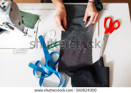 pattern, scissors, tape measure, and a sewing machine. Workplace of seamstress. Seamstress makes the pattern dress. - stock photo