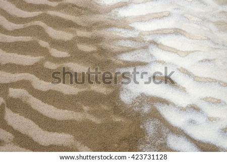 pattern with wet sand ripples and salt deposition on desert dry wash. - stock photo