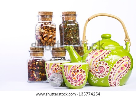 Patterned green pot with two cups and fruit tea