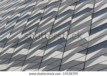 Patterned wall of a modern building made of metal and glass.