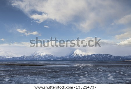 Patterns in Mud Bay at low tide near Homer Alaska with snow covered mountains and clouds.