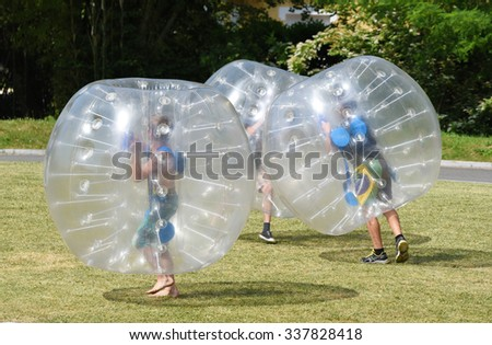 PAU, FRANCE - JUNE 06 2015: Several people play inside of the large transparent plastic spheres (orbs or zorbs) outdoors in the park of PAU, FRANCE - JUNE 06 2015.. - stock photo