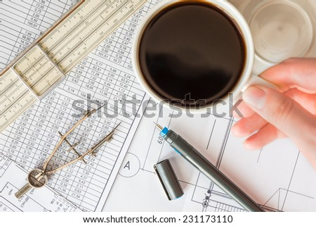 Pause in project development, hand holding a mug of coffee - stock photo