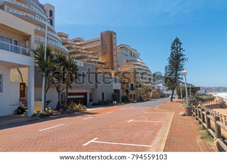 Paved beachfront road between commercial and residential buildings and beach against clear blue sky at Umdloti near Durban, South Africa
