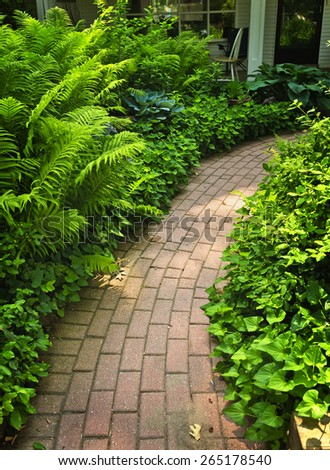 Paved brick path in lush green summer garden - stock photo