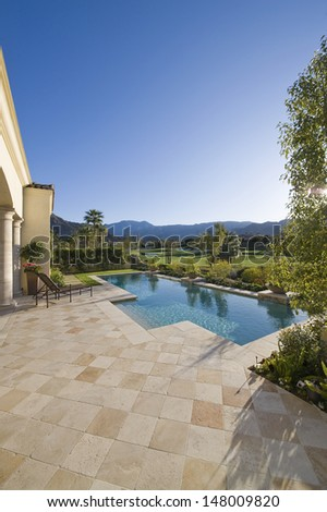 Paved poolside area and summer landscape - stock photo