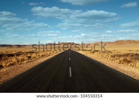 paved road in the desert with clouds Namibia Africa - stock photo