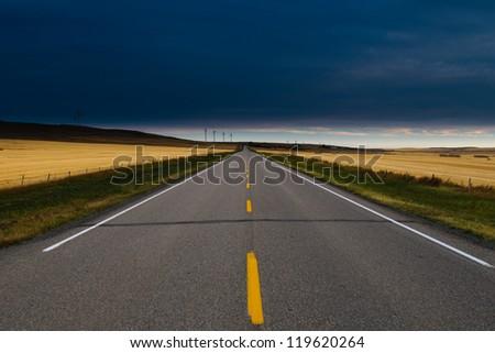 Paved road through Alberta Farmlands with windmills at dawn - stock photo