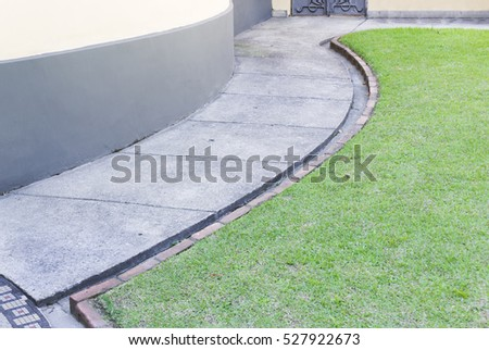 Paved road-winding concrete-circling garden grass