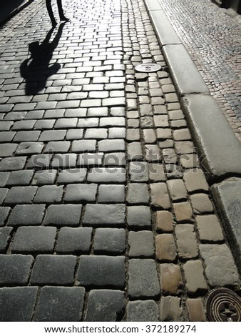 Paved Road With A Human Shadow in Prague, Czech Republic - stock photo