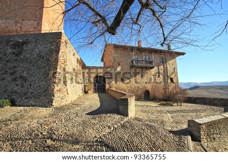 Paved stoned courtyard, old brick house at the entrance to castle in town of Serralunga D'Alba, Northern Italy.