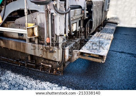 pavement machine laying fresh asphalt or bitumen on top of the gravel base during highway construction or road repairing - stock photo