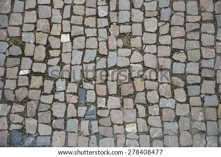 Pavement of grey and pinkish foursquare-similar cobblestones as background.