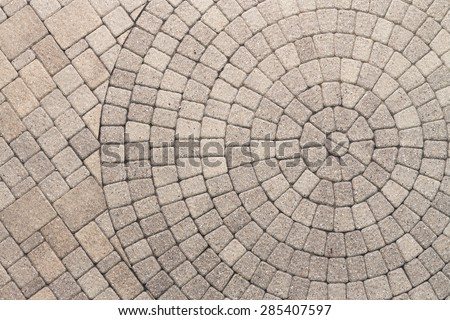Paver bricks arranged in a circular pattern of concentric geometric circles. Architectural background of an ornamental pattern in outdoor patio paving.