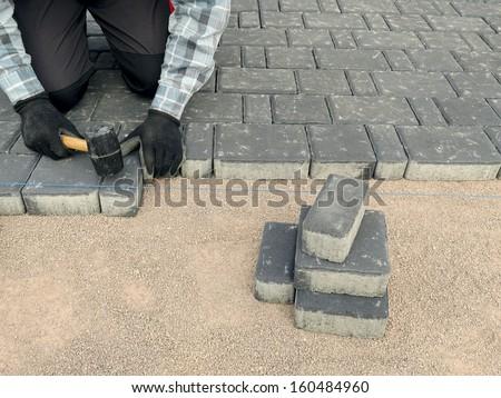 Paver laying driveway pavement out of concrete pavement blocks - stock photo