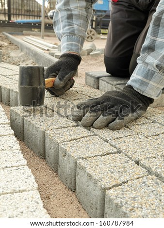 Paver laying pathway out of concrete pavement blocks - stock photo