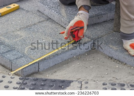 Paver measuring irregular space for laying concrete brick, laying cement blocks. Selective focus.