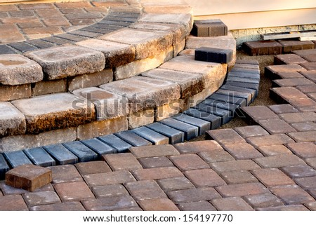 Pavers meets with patio steps and job completion almost done, steps have rain slope - stock photo