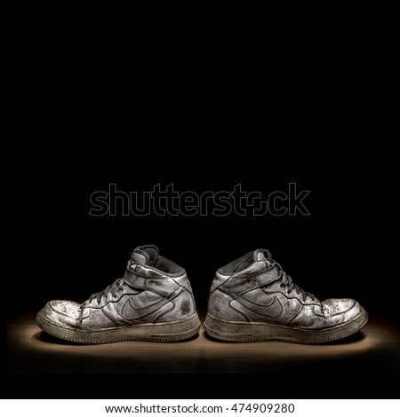 Pavia, Italy - August 28, 2016: Pair of vintage well worn white Nike Air Force One shoes. Taken at studio with lightpainting technique - illustrative editorial