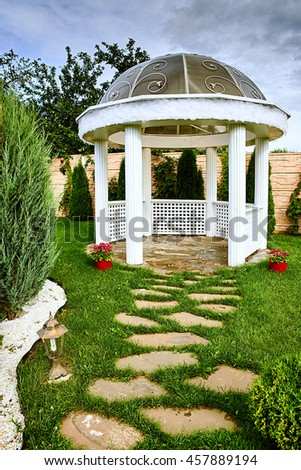 Pavilion in the garden, pergola in an urban garden for recreation, wooden lounge outdoors, peaceful gazebo set in a mature garden, blue sky sunny and cloudy - stock photo