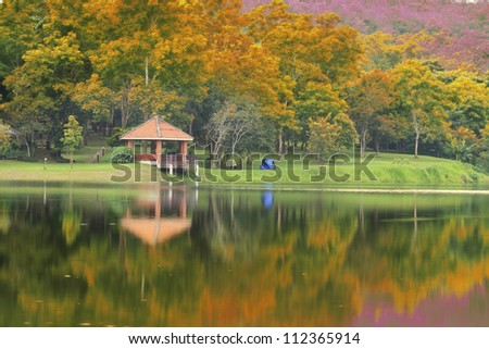 Pavillion in the autumn park with reflex in the river. - stock photo