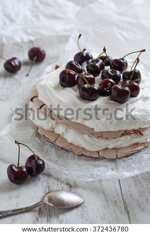 pavlova cake with fresh cherries and cream on the top and a dessert spoon in the foreground - stock photo