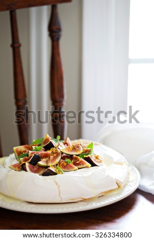 Pavlova cake with fresh figs, white chocolate, ricotta cream and orange zest - stock photo