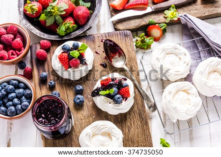 Pavlova traditional dessert with fresh berry fruits. View from above, on wooden table with rustic board. - stock photo