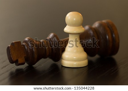 Pawn defeats dark king on wooden table.