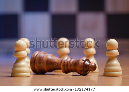 Pawns and a queen on chess board