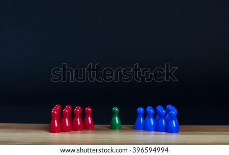 pawns in three colors on a wooden table with black background