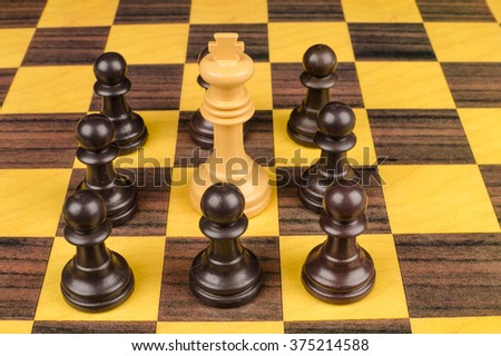 Pawns surrounding king, a social upheaval concept
