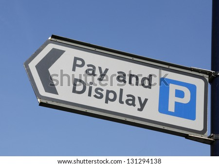 Pay and Display parking sign against a blue sky.