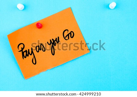 Pay As You Go written on orange paper note pinned on cork board with white thumbtack, copy space available - stock photo