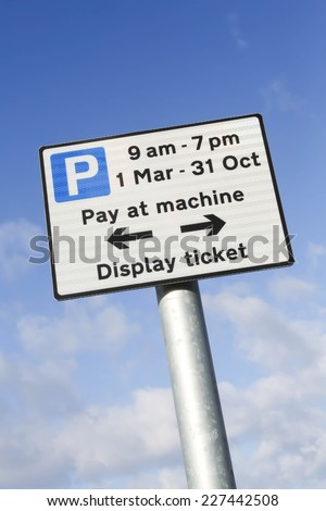 Pay at machine car park sign when parking between 9am and 7pm, March to October against a partly cloudy sky.