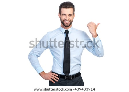 Pay attention to this! Confident young handsome man in shirt and tie pointing away and smiling while standing against white background  - stock photo