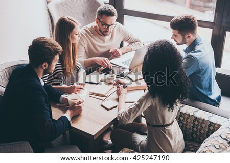 Pay attention to this! Young handsome man pointing at digital tablet while sitting at the office table on business meeting with his coworkers - stock photo