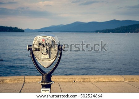 Pay binoculars at Lake George New York. Beautiful golden sunset light contrasts the blue lake and mountains in the background. One of the most popular destinations for vacation in New York State.