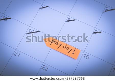 Pay day written on a sticky note on a calendar. - stock photo